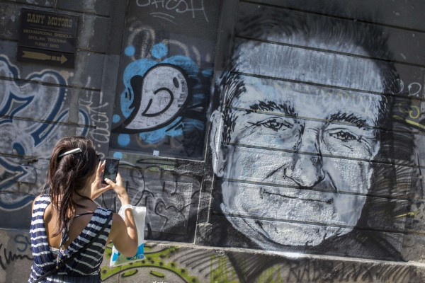 A woman takes a picture of a mural depicting late actor Robin Williams in Belgrade, Aug. 13, 2014. The mural was drawn on a building in downtown Belgrade by an unknown artist on Tuesday.