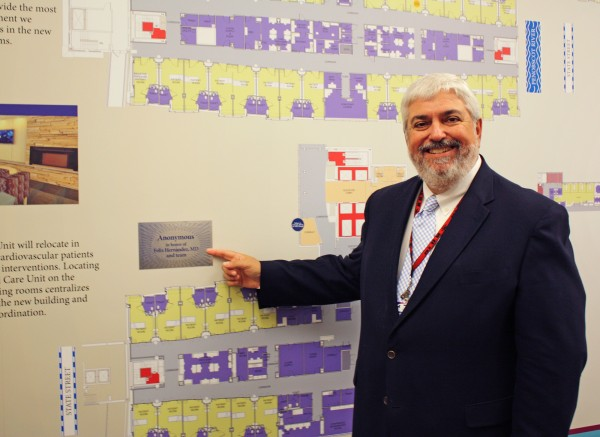 Felix Hernandez, MD, MMM, FACS, medical director of Surgical Services, points to a marker on a wall featuring an overview of EMMC's Modernization Project that highlights the $1 million donation from an anonymous grateful patient in honor or Dr. Hernandez and the team who provided care for the patient.