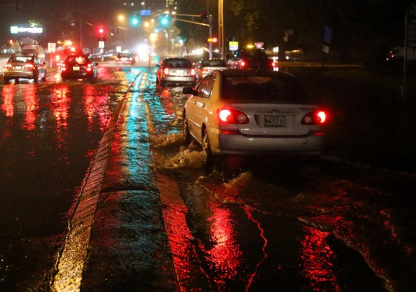 A car approaches the intersection of Forest Avenue and Marginal Way on Wednesday after torrential rains caused widespread flooding in low-lying areas of Portland. Just ahead sit two cars that were abandoned by their drivers.