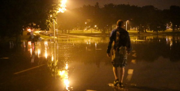 Portland resident Nick Rausch prepares to walk through knee-deep water Wednesday night on State Street in Deering Oaks Park. Water from the duck pond overflowed its banks and poured across the street in the wake of torrential rains.