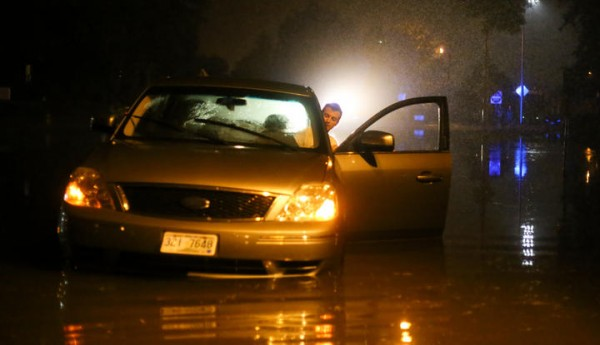 Scarborough resident Adam Chick waits for help Wednesday night in his car, which was disabled by high water on State Street in Portland's Deering Oaks Park. The record-breaking storm dropped more than 6 inches of rain in parts of southern Maine in a few hours, according to the National Weather Service – more than twice the average total for the month of August. Chick said a police officer waved him through and cautioned him to proceed slowly, moments before his car stalled in the water. Chick's was the last vehicle to enter the water before police closed the street.