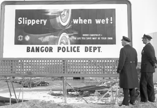 The Bangor Police Department launched a safety program in January 1954. Here, police officers survey a billboard message that was part of the safety campaign.