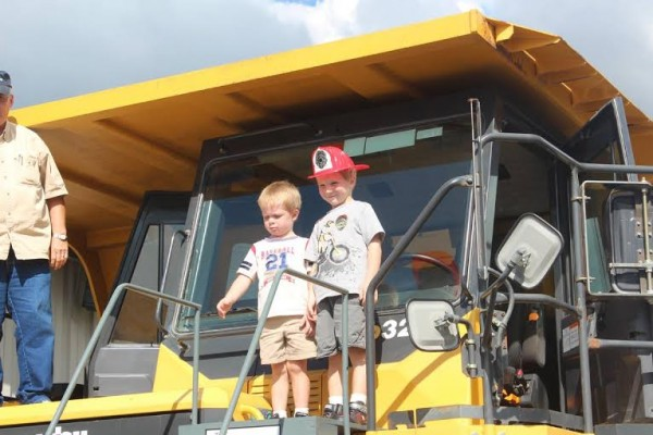 These little boys - future rescue vehicle drivers, perhaps - at last year's Touch-A-Truck event to benefit Camp CaPella, survey the world from the top of a large vehicle.
