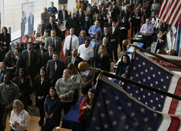 Job applicants listen to a presentation before the start of a job fair for veterans and their spouses in Washington.