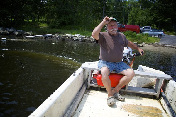 Jesse Leach drives his boat along the Bagaduce River to show his oyster growing operation that he's worked for 17 years.