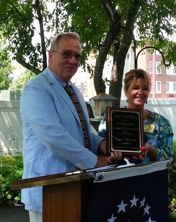 Ed Morin with Market Surveys of America presents the plaque for Best Nursing Facility in Bangor to Brenda Plaumann, director of nurses at the facility.