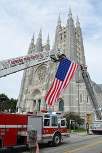Ladder trucks display the American flag outside of the Basilica of Saints Peter and Paul in Lewiston during the 2012 Blue Mass.