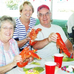 Enjoying their lobster dinner at last year's Habitat Lobster Gala are, seated, Gail and Doug Smith of Belfast, and standing, Carol Robbins of Searsmont.