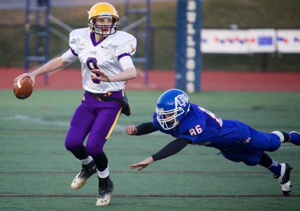 Bucksport High School quarterback Matthew Stewart (left) evades a tackle from Oak Hill High School's Samson Lacroix Saturday in the Class D state football final at Portland's Fitzpatrick Stadium on Nov. 23, 2013.