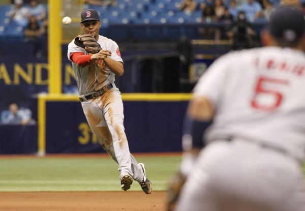 Boston Red Sox shortstop Xander Bogaerts (2) throws the ball to first baseman Allen Craig (5) for an out during the seventh inning against the Tampa Bay Rays at Tropicana Field in St. Petersburg, Florida, Monday.