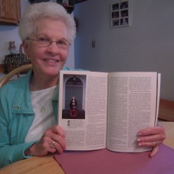 Rita Lannigan of Presque Isle shows the 1980 issue of National Geographic picturing her grandmother, Alma Dube of Lille, mourning the closure of her church, Notre-Dame-du-Mont-Carmel.