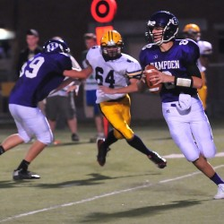 Hampden's Tommy Farrar rolls out while being pursued by Mt. Blue's McKinley Goozey during a game in Hampden on Sept. 5. For more photos from this game,  visit MaineSportsReport.com.