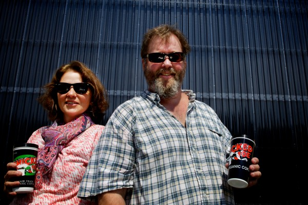 Bob Garver and Carmen Smith Garver, co-owners of Wicked Joe, stand in the sunshine in front of the solar wall at their new facility in a former Navy commissary in Topsham.