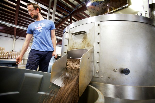 Wicked Joe Roast Master Bill Guddeck lets a batch of roasted coffee out of the roaster and into a barrel in Topsham.