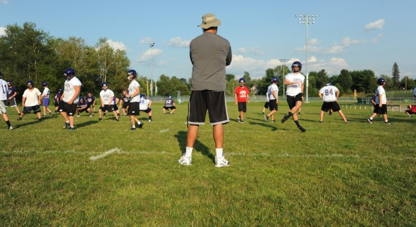 Hampden Academy football coach Kevin Canty keeps a watchful eye over his team during a 2013 preseason practice. The Broncos are building around key veterans on their offensive and defensive lines.