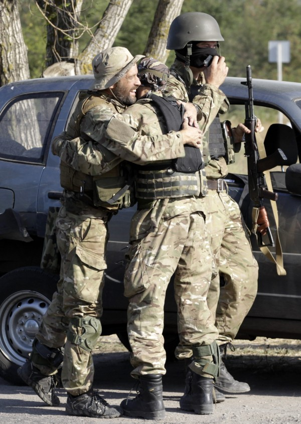 Soldiers of Ukrainian self-defense battalion &quotAzov&quot hug each other as they arrive at a check point in the southern coastal town of Mariupol Sept. 4, 2014. Ukrainian President Petro Poroshenko and the main pro-Russian rebel leader said they would both order ceasefires on Friday, provided that an agreement is signed on a new peace plan to end the five month war in Ukraine's east.