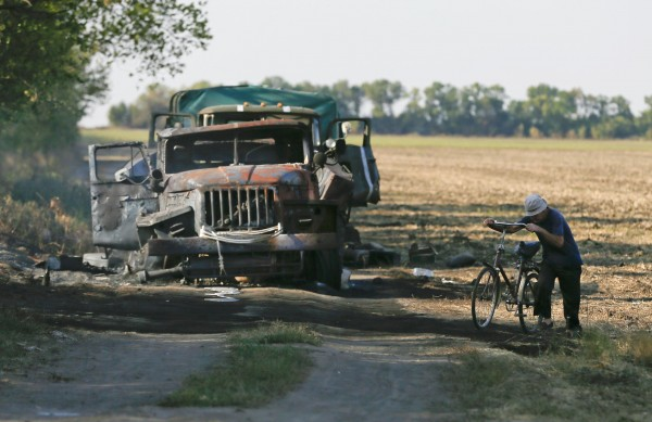 A local resident pushes his bicycle past a burnt truck belonging to Ukrainian forces near the village of Berezove, southwest from Donetsk, Sept. 4, 2014.