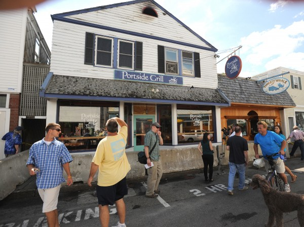 People walk around checking out the fire-damaged Portside Grill on Cottage Street in Bar Harbor on Wednesday. Most of the damage occurred in the back of the building.