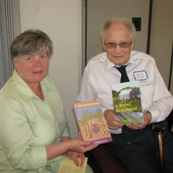 Debbie Sirois and her neighbor Phil Turner with two of the eight books the 92-year-old has published since he retired.
