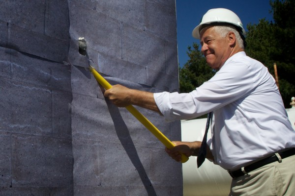 U.S. Rep. Mike Michaud swings a sledgehammer into a ceremonial wall Thursday as redevelopment officials celebrated the unveiling of TechPlace, a manufacturing incubator on the former Navy base in Brunswick.