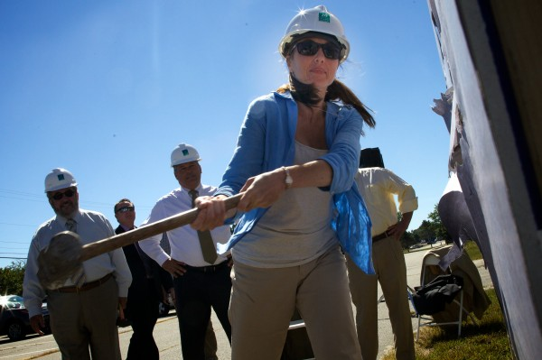 Kristine Schuman, the new administrator of the 93,000-square-foot manufacturing business incubator TechPlace, swings a ceremonial sledgehammer in Brunswick on Thursday.