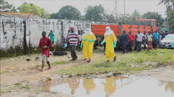 Health workers surround an Ebola patient who escaped from quarantine from Monrovia's Elwa hospital, in the center of Paynesville in this still image taken from a Sept. 1, 2014 video. The patient, who wore a tag showing he had tested positive for Ebola, held a stick and tried to get away from doctors when they arrived on the scene attempting to catch him. The patient was walking through a local market in search of food.