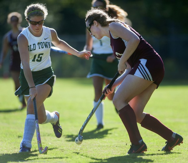 Old Town's MacKenzie Folsom (left) and Jerry Boyer battle for control of the ball during their field hockey game on Wednesday at Old Town.