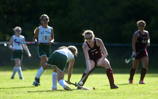 Foxcroft Academy's Jerry Boyer (second to right) and Old Town's MacKenzie Folsom battle for control of the ball during their field hockey game on Wednesday at Old Town.