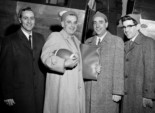 J. Dan Baldwin (second from left), dxecutive director of Bangor's quartquicentennial celebration, hugs a football as he arrives in Bangor after closing negotiations to bring the New York Giants and the Green Bay Packers to Bangor for a pro football exhibition Saturday, Sept. 5, 1959. Shown welcoming Baldwin are (from left) Gordon W. Clapp, chairman of quartquicentennial steering committee; Anthony J. Rogers, local distributor for co-sponsor P. Ballantine & Sons; and Edward J. McInnis, vice president of the Maine Junior Chamber of Commerce, another sponsoring