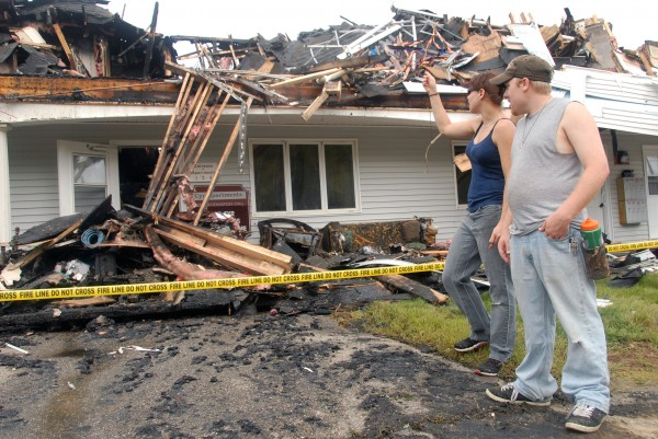 Cassie Kunkel (left) and her husband, Kenny, help salvage items from a destroyed apartment building on Tuesday in Millinocket.