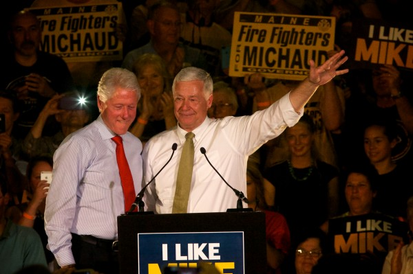 Former President Bill Clinton (left) and Maine gubernatorial candidate Mike Michaud hit the stage at the Portland Expo on Tuesday night in Portland.