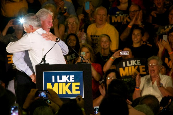 Rep. Mike Michaud (right) gets a hug from former President Bill Clinton at a Tuesday rally at the Portland Expo.