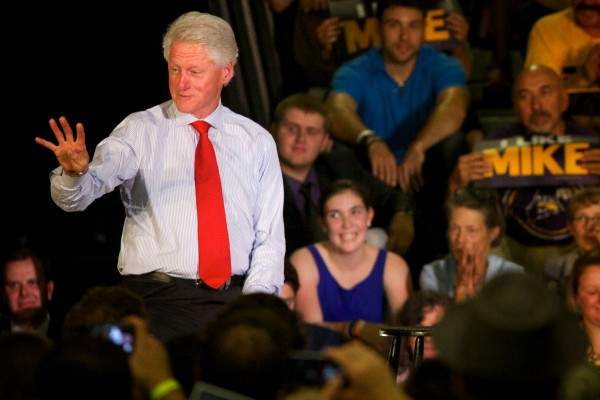 Bill Clinton gestures &quotfour times&quot when a woman from the crowd called out that he had balanced the federal budget while president at a Tuesday night rally in Portland.