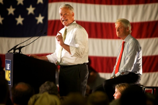 Former President Bill Clinton (right) listens as Maine gubernatorial candidate Mike Michaud speaks on Tuesday at the Portland Expo.