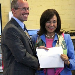 UNE President Danielle N. Ripich hands Thornton Academy Headmaster Rene M. Menard the official agreement.