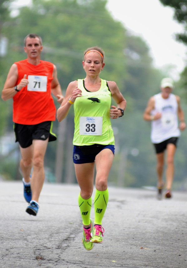 Sarah Mulcahy of Baring Plantation,  runs down West Broadway with Greg Dean behind her in the 52nd annual Labor Day 5-Mile Road Race.  This was Mulcahy's first race since the birth of her baby two months ago and she placed first for women and 11th overall with a time of 32:12.
