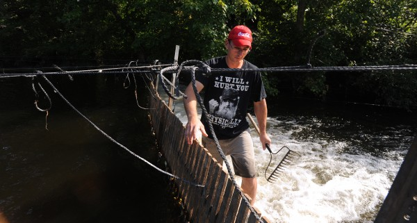 Theodore &quotT.J.&quot Whitten walks along the eel weir with a rake to check for obstructions to the water flow on Aug. 27.