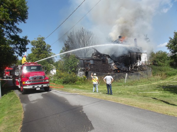 Firefighters pour water on a burning home in Machias. No one was home at the time the fire erupted.