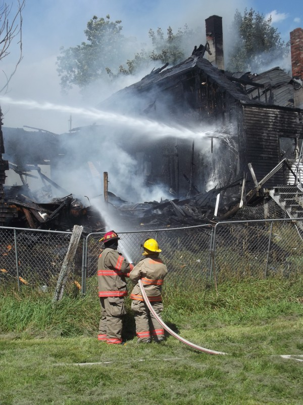 Firefighters pour water on burning home in Machias. No one was home at the time the fire erupted. An adjacent barn also was destroyed.