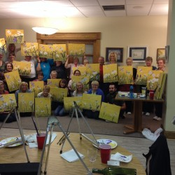 A group of talented Paint Night artists pose with their work at the end of the evening.  Many are first time artists and all range in age.