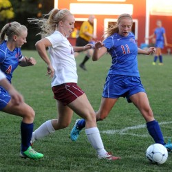 Bangor High School's Sarah Bragg (center) drives up the field between Messalonskee High School's Taylor Lenentine (left) and Cassidy Charette (right) during the first half of the game in Bangor in September 2014.