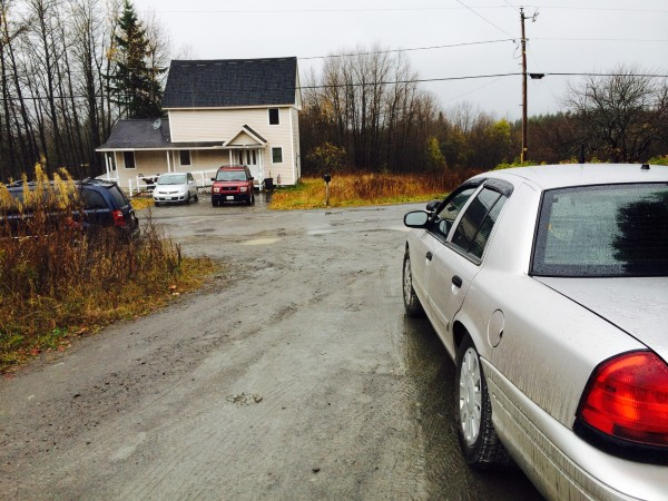 A Maine State Police trooper sits in an unmarked car (foreground) on Wednesday across the street from the rural Fort Kent home of Kaci Hickox.