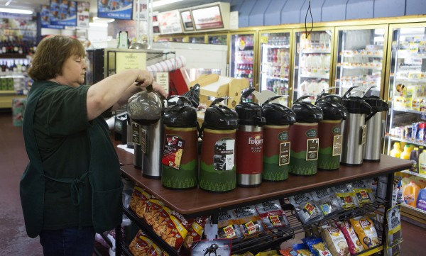 Tozier's employee Joyce Achorn refills the coffee on Wednesday at the store in Bucksport. After the announcement of the Verso paper mill closing, the future of many local business is uncertain.