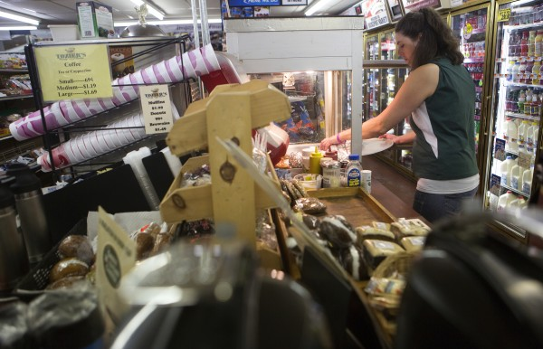 Tozier's employee Rosie Fish fills a case with fried hot dogs on Wednesday at the store in Bucksport. After the announcement of the Verso Paper mill closing, the future of many local business is uncertain.