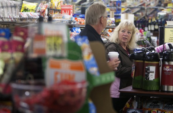 Tozier's owner Dale Tozier (left) talks with Holly Smith on Wednesday at the store in Bucksport. After the announcement of the Verso paper mill closing, the future of many local business is uncertain.