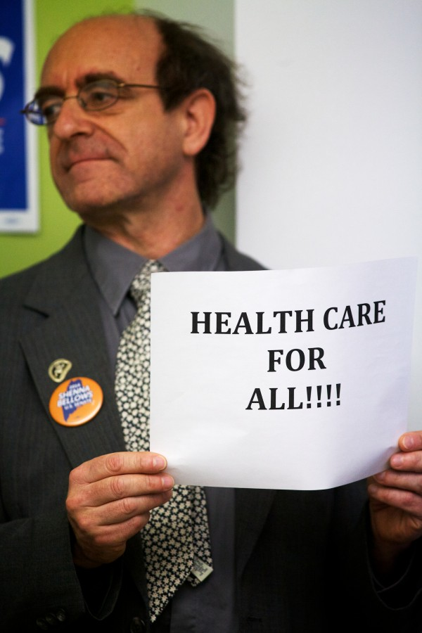 Seth Berner of Portland holds a sign at a press conference Thursday morning in Portland, where Democratic U.S. Senate candidate Shenna Bellows spoke of her support for a universal health care program while criticizing incumbent Sen. Susan Collins' votes to repeal the Affordable Care Act.