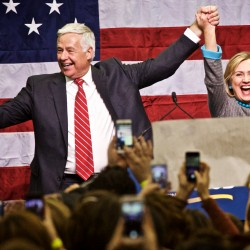Democratic nominee for governor Mike Michaud and Hillary Clinton stand hand in hand at the podium during a political rally on Friday at Scarborough High School.