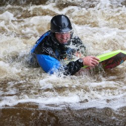 "Justin Davis body surfs down the Kenduskeag Stream Thursday in Bangor. ""We go out whenever the water comes up,"" said Davis. ""When the water comes up, it brings the magic."""