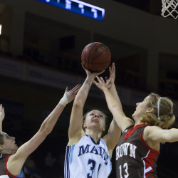 Liz Wood (center) of the University of Maine goes up for a shot between Brown University's Ellise Sharpe (left) and Jordin Alexander during their basketball game Saturday at the Cross Insurance Center in Bangor. The Black Bears won 58-53.