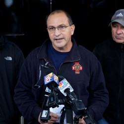 Portland Fire Chief Jerome LaMoria (center) speaks to the media Saturday confirming five people died in a structure fire on Noyes Street earlier in the day. Police Chief Michael Sauschuck (left) and Mayor Michael Brennan stand on either side.